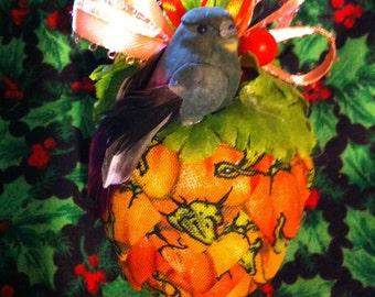 Orange pumpkin print fabric pinecone ornament.
