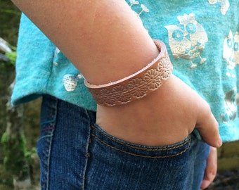 1/2 inch wide diffuser bracelet for aromatherapy - natural leather tooled with a repeating floral design and sealed with pearl topcoat