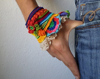 freeform crochet cuff with yellow, orange, red, turquoise blue, indigo and green beaded flowers