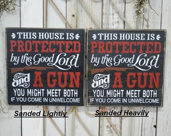 IN STOCK~  This house is protected by the good Lord and a gun you might meet both  12x12 Solid Wood Sign Choose distressing & hanger