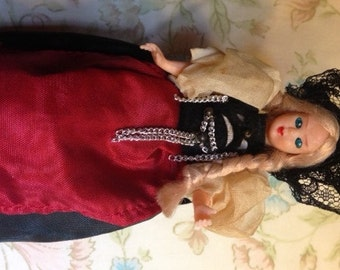 "Antique Doll 5"" old European costume, red apron, puffy sleeves, black lace hat, long blond braids, sleepy eyes"
