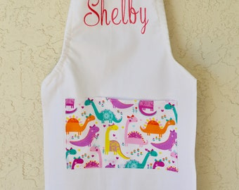 Personalized kids apron dinosaur print includes name and pocket.