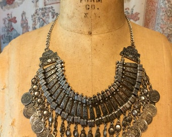 Silver tone metal bib necklace with decorative coin fringe