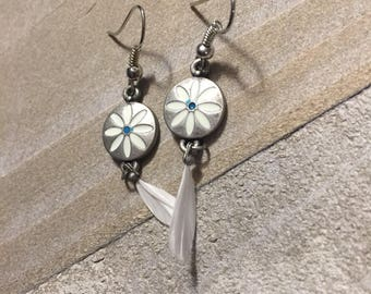 Brushed silver circle w/ white etched flower design and small white feather dangle