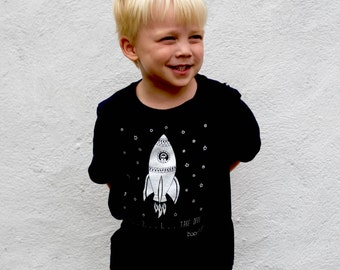 Space organic kids T-shirt, perfect for all those space lovers. Featuring a space rocket taking off with an astronaut, surrounded by stars.