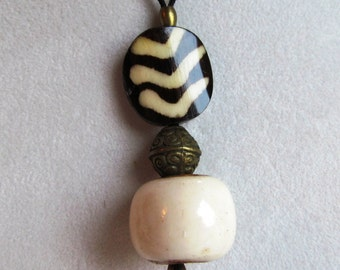 Pendant of Hand Batiked Bone Coin, Brass Bicone and White Bone Drum Beads Silk