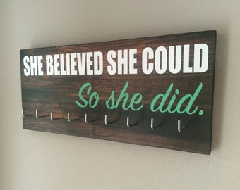"""Race Medal Holder - """"She believed she could SO SHE DID"""" white and teal with wood grain background"""