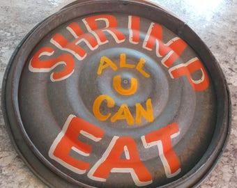 """Vintage metal lid with hand painted """"shrimp all you can eat"""" sign"""