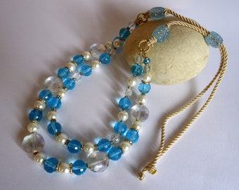 Double necklace made with blue glass crystals and white glass beads. Closure with adjustable cotton cord.