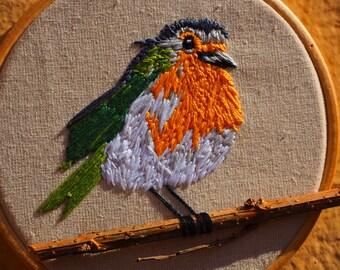 Orange bird hand embroidery in branch
