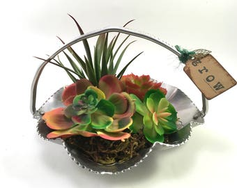 Faux succulent plant arrangement in mid-century scalloped aluminum basket labeled 'grow' with leaf charm