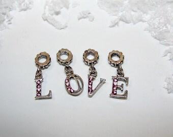 "Charm ""LOVE"" in silver, pale pink rhinestones. Tassel."