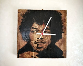 Wall clock made with recycled wood reproducing Jimi Hendrix face