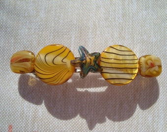 "Barrette is yellow, yellow, yellow and a little blue in the star with stripe shell disks, lampwork glass star and rectangles on 3"" hair clip"