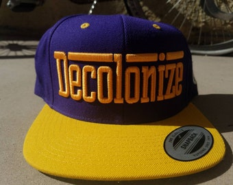 The Decolonize Hat purp and gold