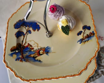 A very sweet vintage shabby chic 2 tier cake stand, decorated with a stylized art deco country scene. Perfect for tea time! c.1930