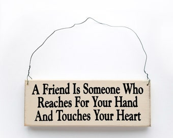 """Wood Sign Saying """"A Friend is Someone Who...Touches Your Heart""""  White Wood Sign With Saying in Black Lettering."""