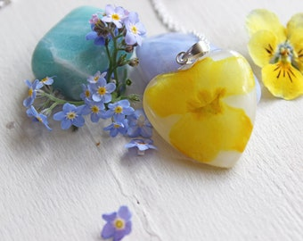 Heart pendant with white resin inlaid with a dark yellow Primrose flower
