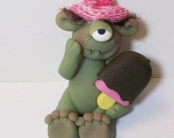 One eyed ice cream monster with brown hair and striped pink hat. polymer clay monster