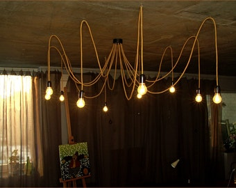 Golden chandelier with twelve textile covered cables. Ceiling octopus or spider.