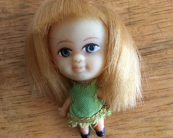 Tiny vintage doll with green dress