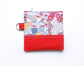 Small coin purse/zipper pouch in flowers and geometric shapes in red, grey and yellow with a red accent, with a light grey zip