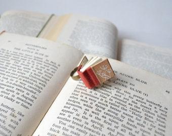Anello con libro arancione  e fiori di tarassaco / soffioni . Anello con libro vero in miniatura