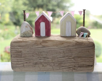 red and yellow beach huts on chunky driftwood.