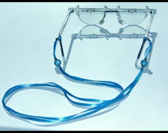 Light blue eyeglass or sunglass cord in satin ribbon and crystal pavè beads. Unique, lightweight and bright.
