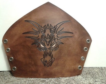 Antique brown leather bracer with hand carved dragon face