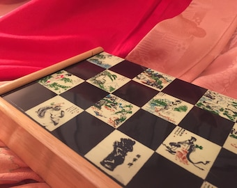 Vintage Folding Chess board adorned with Japanese artwork and figures Natural color wood with plastic overlay surface