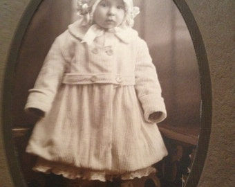 """Antique Photograph of a Little Toddler Baby Girl in Coat and Hat Standing Oval Picture in large 6-1/2"""" x 11"""" Folder"""