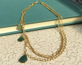 Layered chain necklace featuring three golden accents drops with resin and sand.