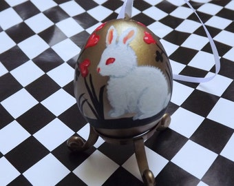 White Rabbit Easter Egg. Shiny gold eggshell ornament with an Alice in Wonderland theme.