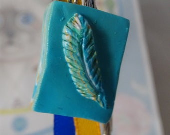 writer's feather bookmark on leaves
