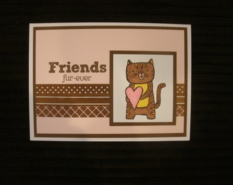Friends Furever Card with cat holding heart & ribbon accents