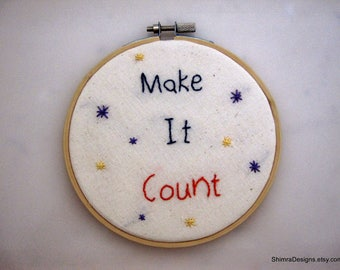 "Embroidery Hoop Wall Art Featuring ""Make It Count"" in Blue and Ornage on 100% Off White Cotton and Decorated with Purple and Yellow Starts"