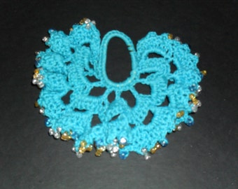 Hand crocheted hair scrunchie with gold and silver plastic beads and elastic band.