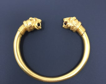 Gold tone cuff bracelet with lion heads