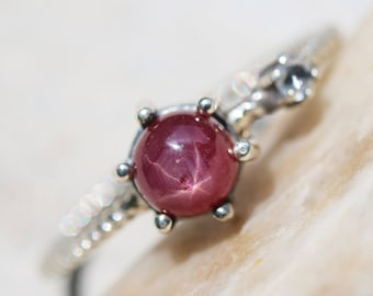 Round cabochon star ruby ring in silver bezel and prongs setting with white sapphire on the side with sterling silver twist design band