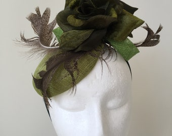 Sophisticated green fascinator with round base and flowers and feathers. Stunning on!