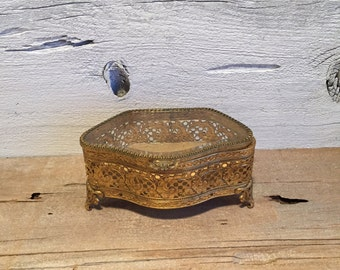 Gold filigree jewelry box with beveled glass lid.