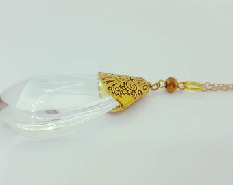 Clear glass pendant necklace with gold tone bead