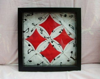 Cathedral Window patchwork textile art in black box frame.