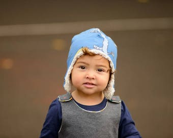 Aviator Winter hat in organic cotton jersey lined with organic unbleached cotton plush. Animal Hotel on Blue