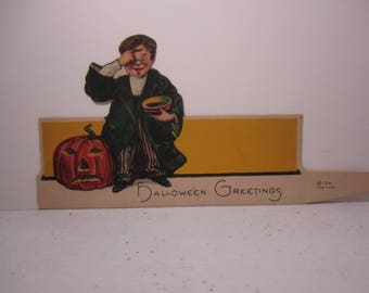 Colorful Die cut unused 1920's Hallmark Halloween Place card boy marking his face with black ash standing next to jack o'lantern