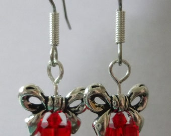 Red earrings that look like gift wrapped packages with silver bows