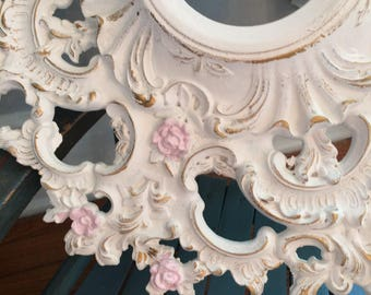 A vintage flowered baroque white ceiling medallion, gold highlights, pink flowers, nursery