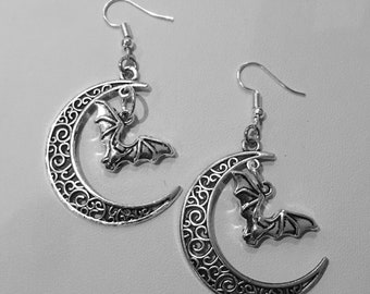 Silver moon and flying bat silhouette drop earrings.