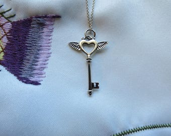 Sterling Silver Flying Key Pendant with delicate wings and heart-shaped center accompanied by a Sterling Silver Chain!